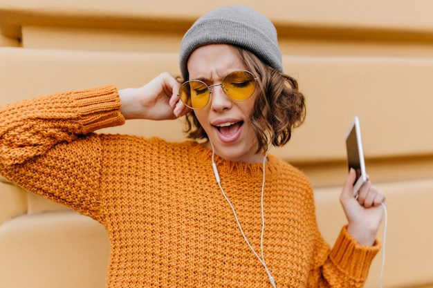 Funny female model with short curly hair singing favorite song while standing on the street with smartphone