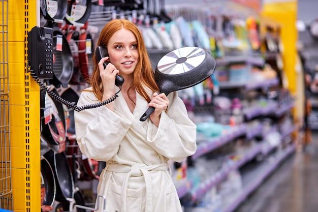手に鍋を持って、バスローブを着て店で電話で面白い女性の話