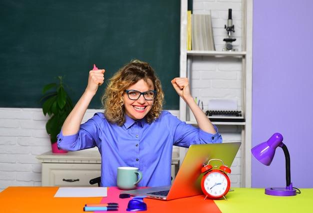 教室の面白い女性の若い先生は、テーブルの大学生でカジュアルな女の子の学生を興奮させました