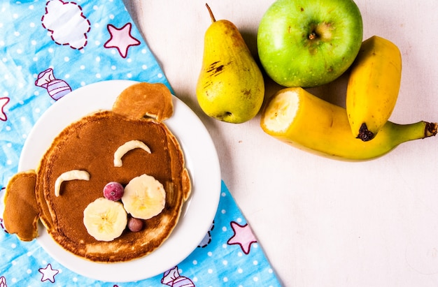 Funny food for children, breakfast pancakes in the shape of a dog's snout. with banana and berries, fresh fruits are near.