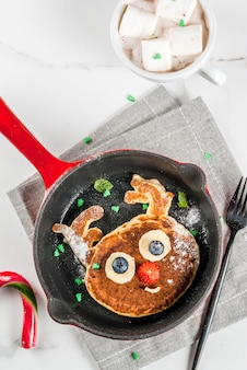 Funny food for christmas. kids breakfast pancake decorated like reindeer, with hot chocolate with marshmallow, white table