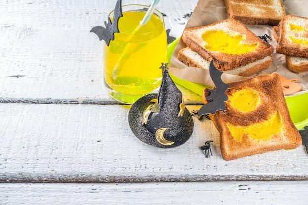 子供のための面白い食べ物、ハロウィーンの朝食、ランチボックス:ハロウィーンのモンスターや幽霊の形をしたスクランブルエッグのトースト、装飾が施された木製のテーブル、上面図、コピースペース