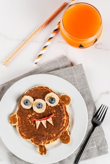 Funny food for halloween. kids breakfast pancake decorated like creepy monster, with banana, berries, with pumpkin smoothie juice, white table