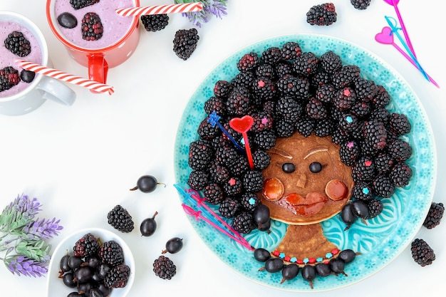Funny food idea for children edible african girl, face from pancake, gooseberry and blackberry