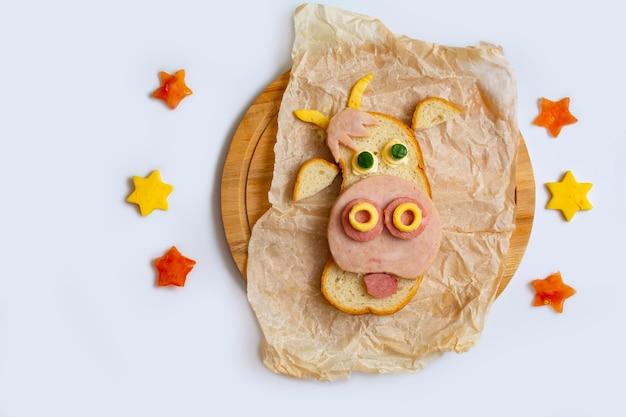 Смешная еда со съедобным символом бычьей коровы из хлеба, сыра и овощей