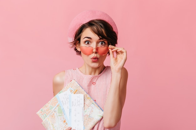 Signora francese divertente in attesa di viaggio sulla parete rosa
