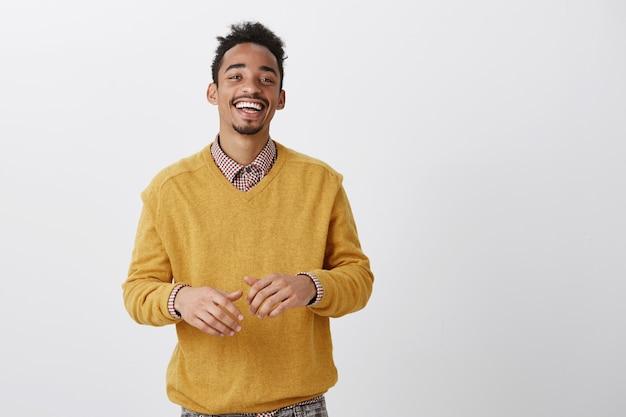 Un amico divertente racconta barzellette esilaranti. tiro al coperto di felice afro-americano felice in abito elegante sorridente ampiamente e gesticolando sul petto durante la conversazione, avendo una bella chiacchierata con il collega