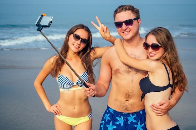 재미있는 친구가 해변에서 셀프 스틱으로 사진을 찍습니다.