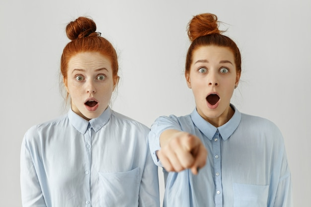 Funny frightened sisters wearing identical hair knot and light-blue shirts having shocked looks, scared with horror movie they watching together at home, one of girls pointing finger
