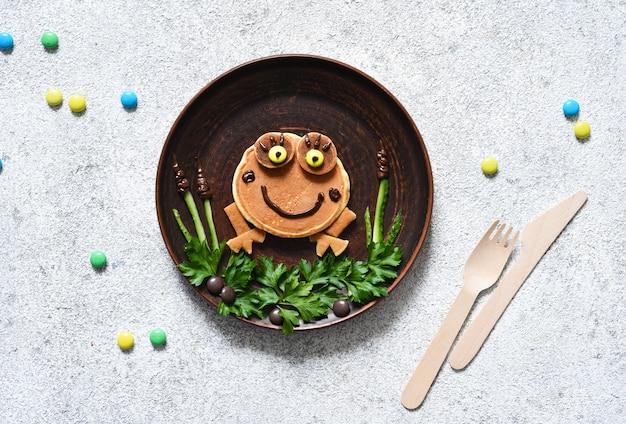 Забавная лягушка из блинов на тарелке, вид сверху. завтрак для детей.