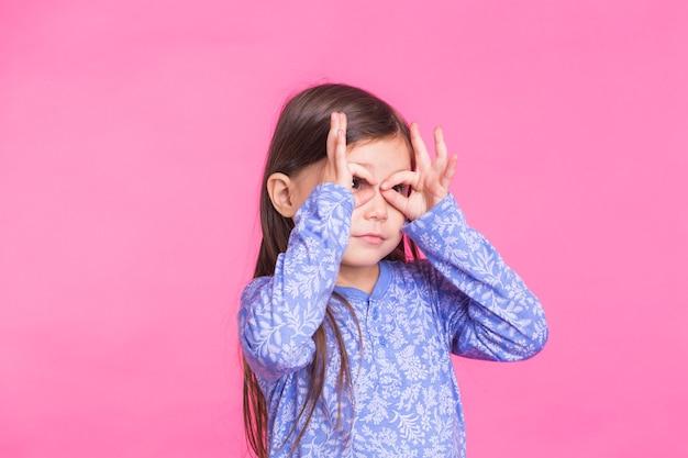 指でメガネを作っている面白いファンキーで楽しいかわいい赤ちゃんの子供の女の子