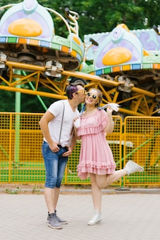 Funny funny and funny couple in love a guy and a girl in sunglasses are smiling and happy in an amusement park