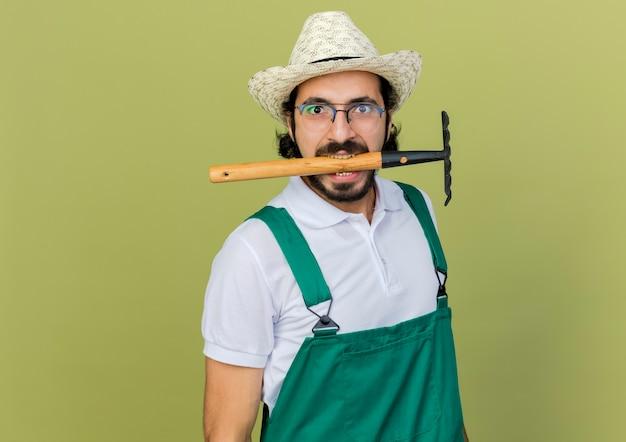 원예 모자를 쓰고 광학 안경에 재미있는 정원사 남자는 이빨을 가진 갈퀴를 보유하고 있습니다.