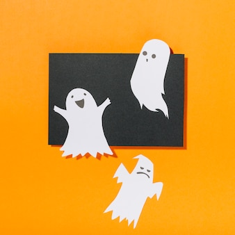 Funny ghosts on piece of black paper