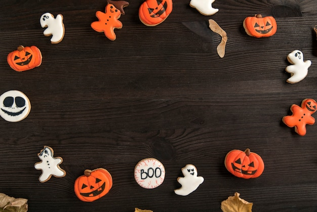 カボチャ、ゴースト、スマイリーの形でテーブルにハロウィーンのための面白い生姜クッキー。上面図。テキスト用のスペース