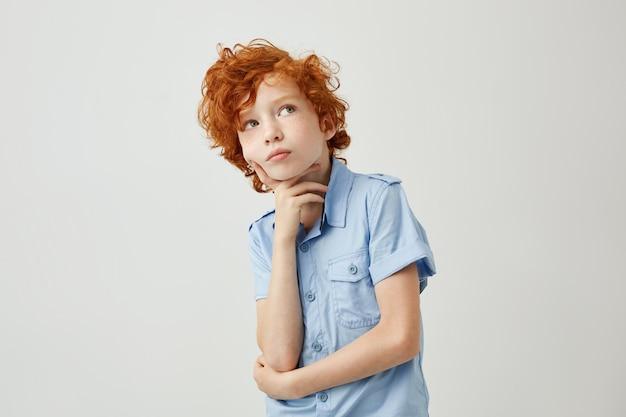 Забавный рыжий маленький мальчик с волнистыми волосами и веснушками мечтательно смотрит в сторону, пытаясь вспомнить