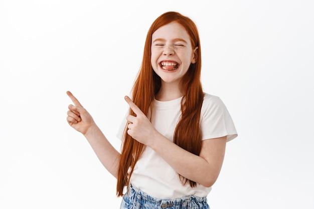 Смешная рыжая девочка показывает в сторону верхний левый угол, улыбается и показывает язык с довольным детским выражением лица