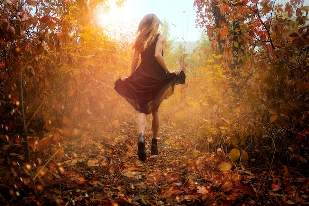 Funny girl in black dress running in golden autum forest outdoors
