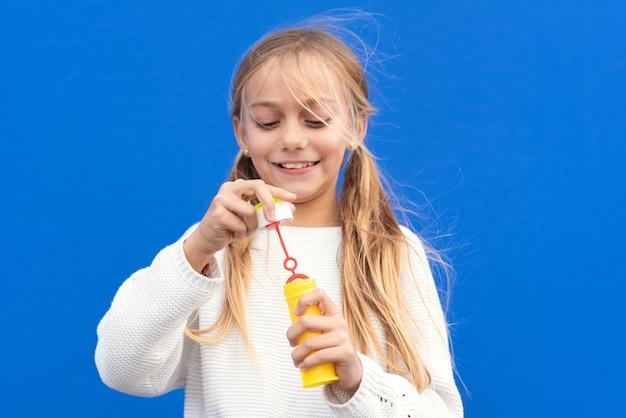 Смешная девочка дует мыльные пузыри, изолированные на синем фоне