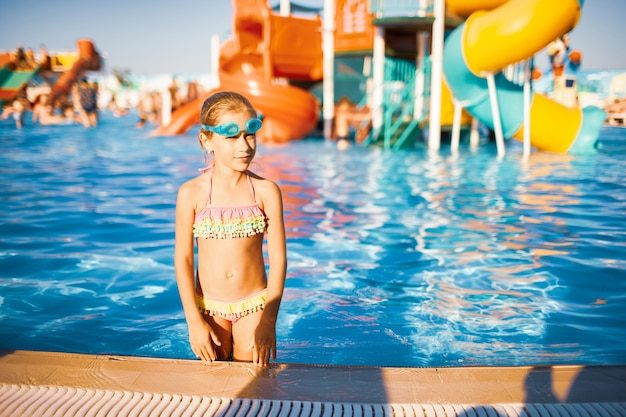 Funny girl in blue goggles for swimming stands in a pool with clean transparent water looking at the camera