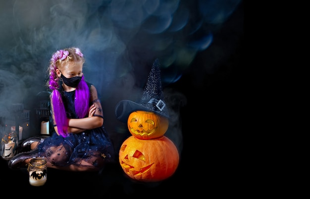 Funny girl in a carnival costume playing with jack o lantern pumpkins and candles in the room.