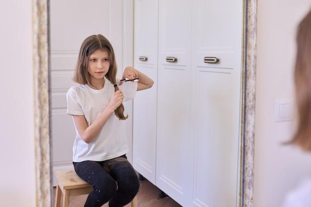 Забавная девочка, стрижущая волосы ножницами, сидя дома перед зеркалом. красота, прическа, эмоции, дети