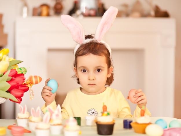 バニーの耳を身に着けて、家でイースターエッグを手にした面白い女の子の子供。