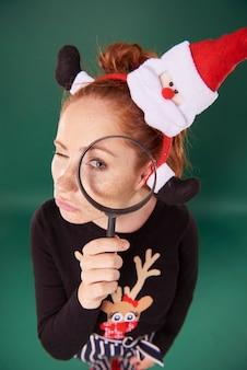 Ragazza divertente in abiti natalizi guardando attraverso la lente d'ingrandimento