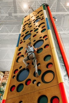 Забавная девочка скалолазание в детском игровом центре