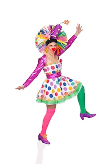 Funny girl clown with a big colorful wig dancing isolated on white background