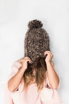 Funny girl covering her face with winter hat