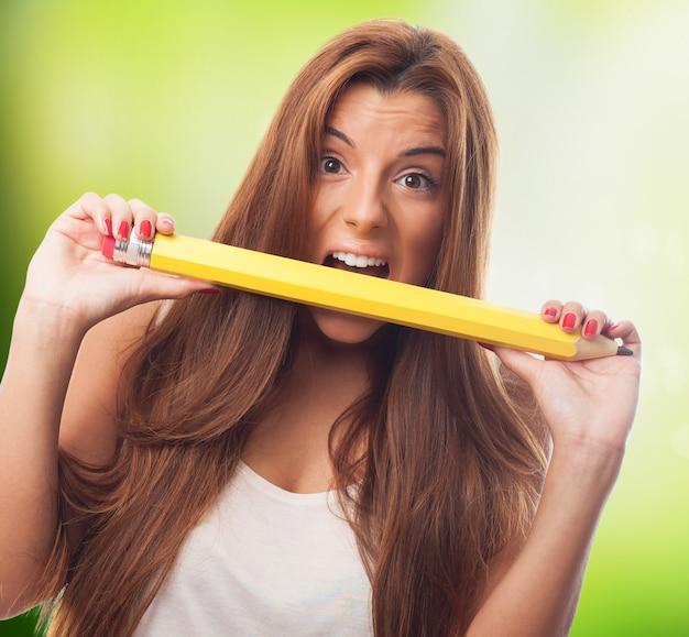 黄色の鉛筆を噛み砕くおかしい女の子。