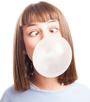 Funny girl doing a bubble with chewing gum