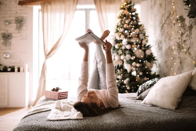 흰색 스웨터와 바지를 입은 재미있는 소녀는 새해 나무가 있는 장식된 방에서 회색 담요, 흰색 베개, 새해 선물로 침대에 누워 책을 읽습니다. .