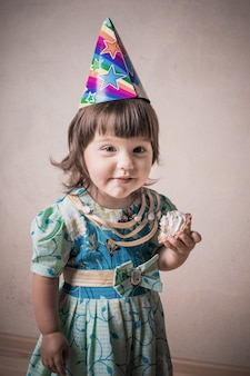 Смешная девчонка ест торт в праздничной кепке в винтажном стиле