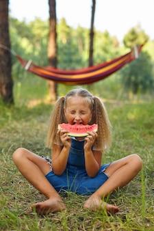 公園でスイカを食べる面白い女の子。子供は屋外で果物を食べます。子供のための健康的なスナック。スイカのスライスを噛んで森で遊んでいる少女