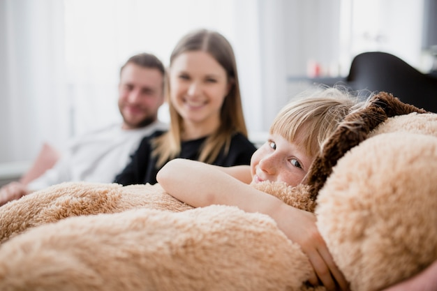 Funny girl embracing toy near parents