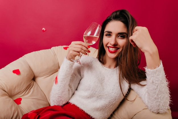 Funny girl in fluffy sweater sitting on cozy sofa and laughing