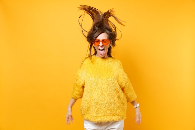 Funny girl in fur sweater, heart orange glasses showing tongue, fooling around in studio jump with fluttering hair isolated on yellow background. people sincere emotions, lifestyle. advertising area.
