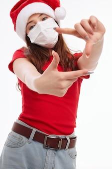 Забавная девочка, показывающая ее руками медицинская маска красная футболка праздник. фото высокого качества