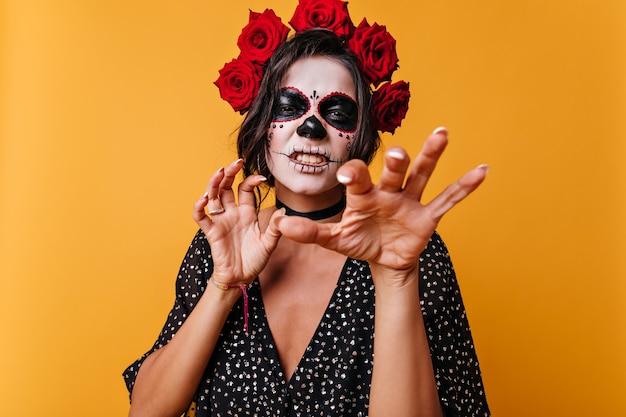 웃기는 소녀는 으르렁 거리며 고양이처럼 손톱을 보여줍니다. 할로윈 메이크업으로 아름 다운 멕시코의 초상화입니다.