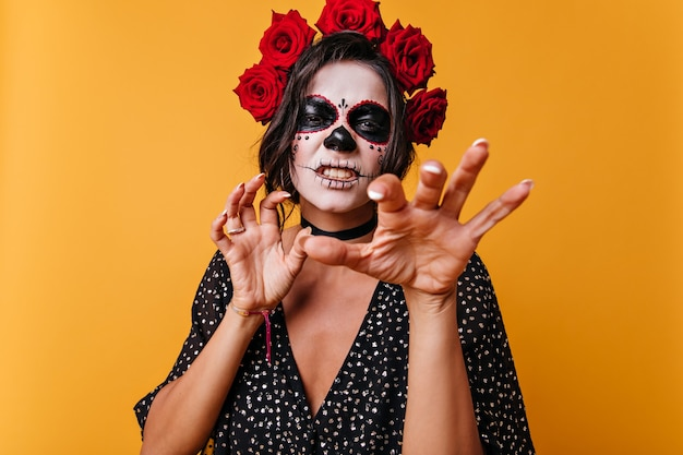 Funny girl growls and shows nails like cat. portrait of beautiful mexican with makeup for halloween.