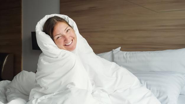白い毛布で隠された面白い女の子は、朝のクローズアップで快適なホテルの部屋の柔らかいクイーンサイズのベッドで楽しんでいます