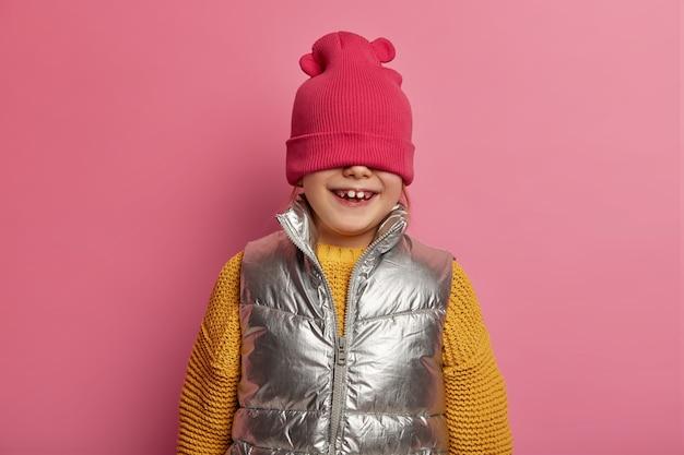 웃긴 소녀는 모자로 얼굴을 숨기고, 긍정적으로 킥킥 웃으며, 어리석은 짓을하고, 니트 노란색 스웨터와 조끼를 입고, 분홍색 벽에 실내 포즈를 취하고, 행복한 감정을 표현합니다. 장난 꾸러기 아이 실내