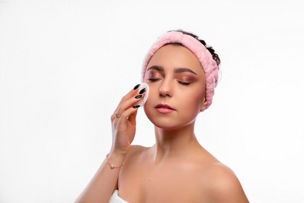 Смешная девочка держит розовую губку возле ее лица. портрет молодой афро-американской девушки на белой стене. концепция ухода за молодостью и кожей.