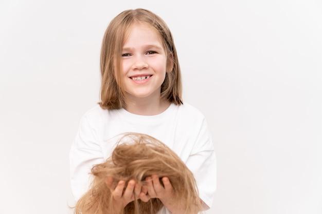 面白い女の子は、白い背景の上のトリミングされた髪を手に持っています。子供の髪の世話をすることを意味します。