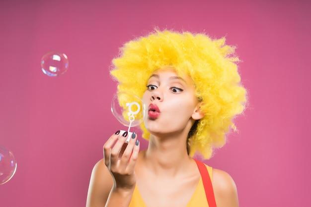 분홍색 배경에 비누방울을 부는 밝은 노란색 가발을 쓴 재미있는 소녀