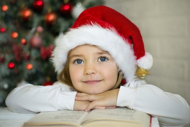 サンタの帽子をかぶったおかしな女の子がクリスマスツリーの近くのサンタに手紙を書いて本を読む