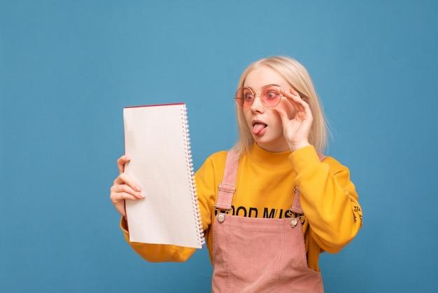 Смешная девчонка в яркой одежде и розовых очках читает изумленную тетрадь на синем фоне