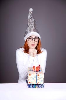 ギフトボックスとクリスマスキャップの面白い女の子